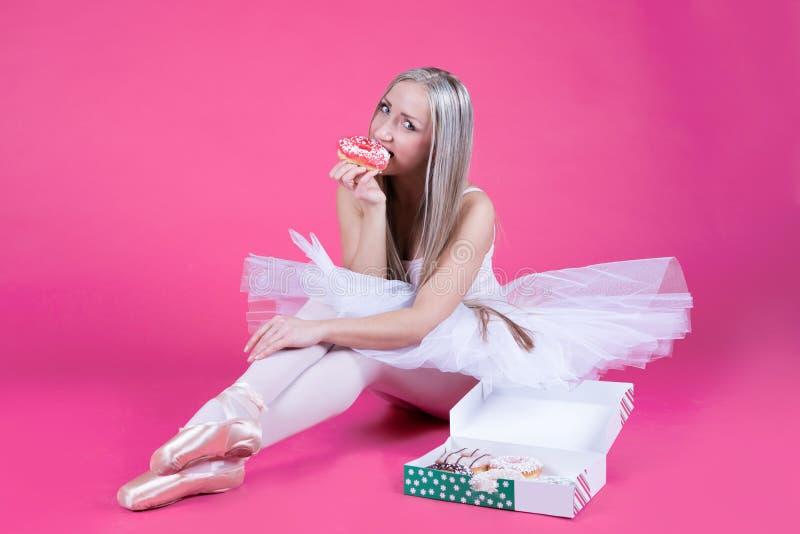 Bailarina na saia do tutu que come uma filhós fotografia de stock