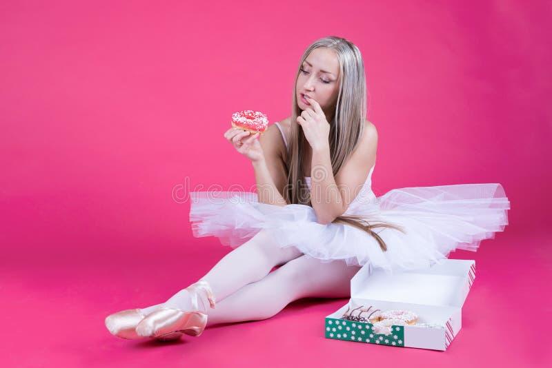 Bailarina na saia do tutu que olha uma filhós fotos de stock royalty free