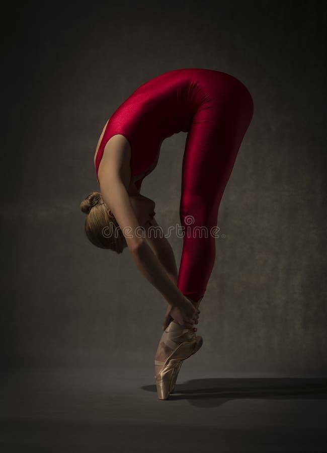 Bailarina no equipamento vermelho que levanta nos dedos do pé fotos de stock