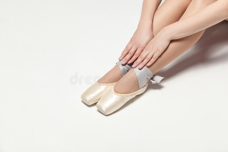 A bailarina no pointe calça o assento no assoalho branco, close up imagens de stock
