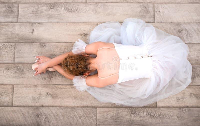Bailarina nova em sapatas do pointe no assoalho imagem de stock