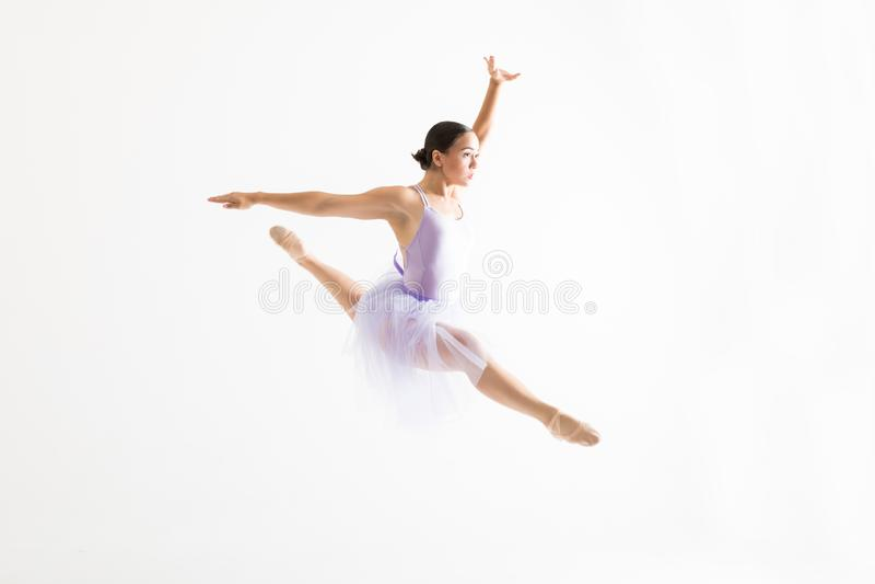 Bailarina nova que faz separações no ar contra o fundo branco fotografia de stock royalty free