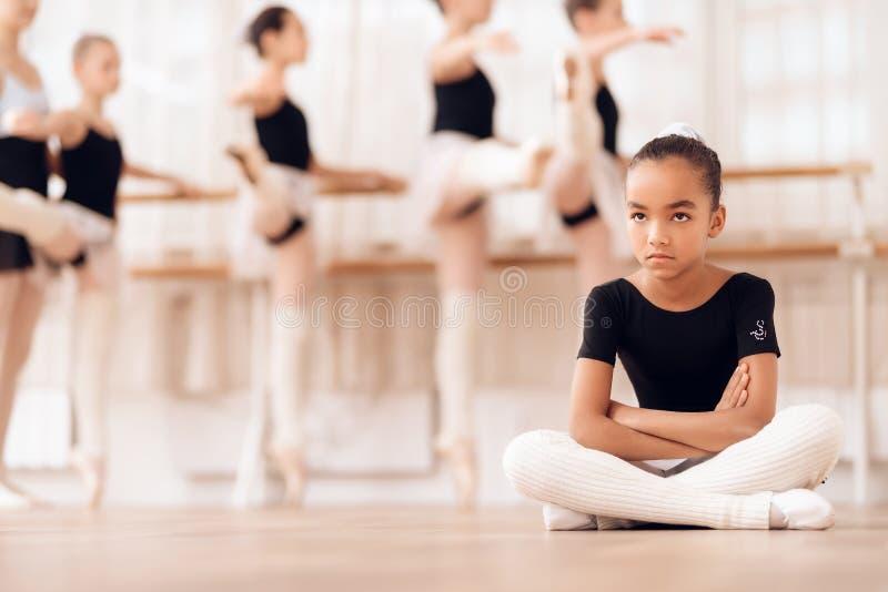 A bailarina nova senta-se no assoalho ao atender a uma escola do bailado fotos de stock royalty free