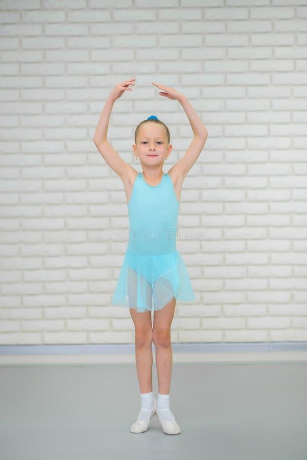 A bailarina pequena em sapatas azuis do vestido e do pointe está dançando na escola do bailado Menina bonito na classe de dança fotos de stock royalty free
