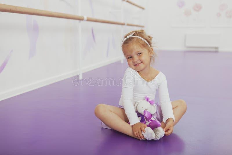 Bailarina pequena feliz bonito que exercita na escola de dança imagem de stock