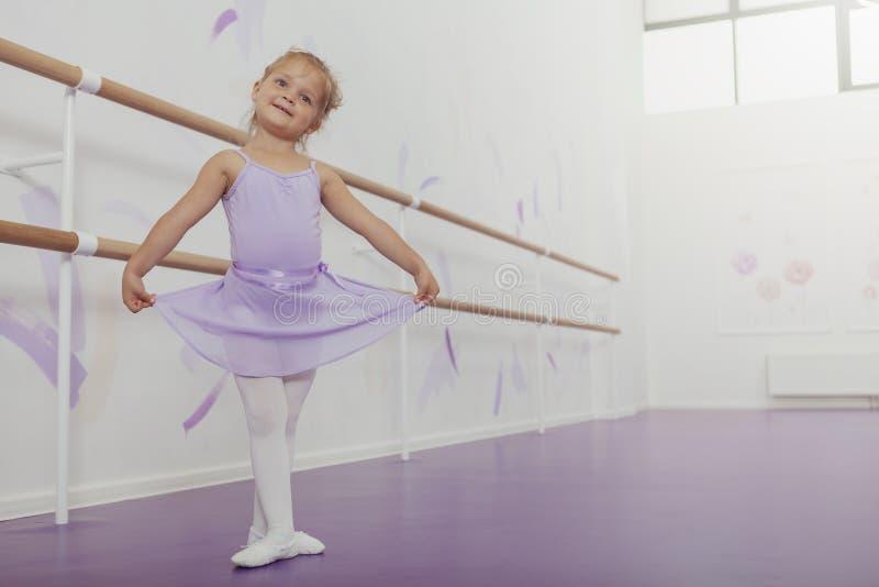 Bailarina pequena feliz bonito que exercita na escola de dança imagens de stock