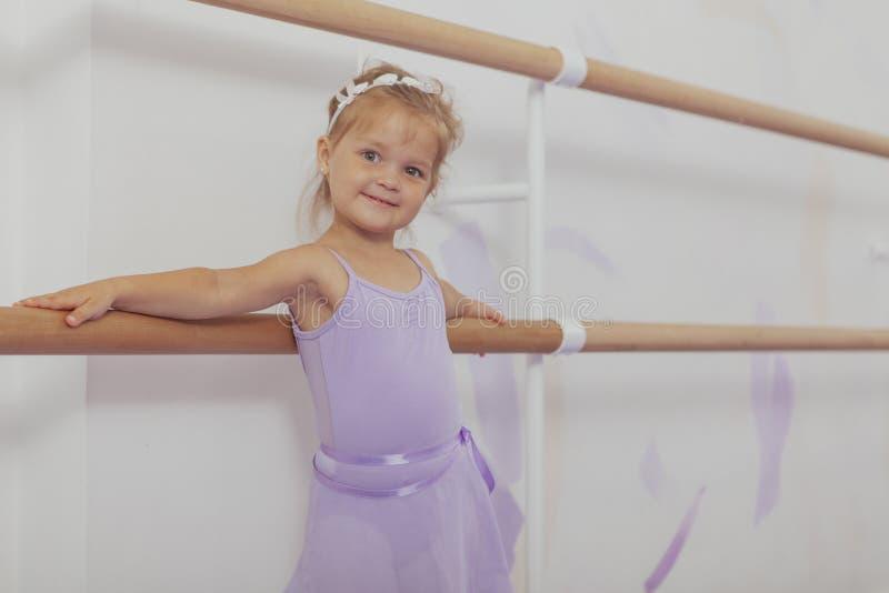Bailarina pequena feliz bonito que exercita na escola de dança imagens de stock royalty free