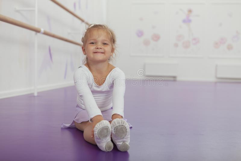 Bailarina pequena feliz bonito que exercita na escola de dança foto de stock