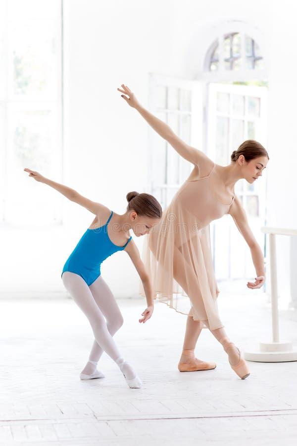 A bailarina pequena que levanta na barra do bailado com o professor pessoal no estúdio da dança fotografia de stock royalty free