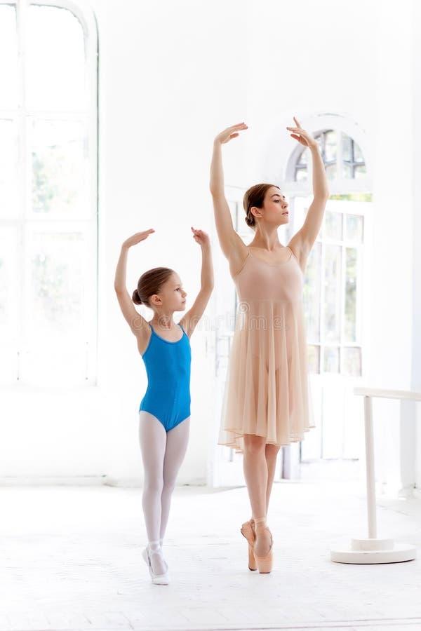 A bailarina pequena que levanta na barra do bailado com o professor pessoal no estúdio da dança foto de stock