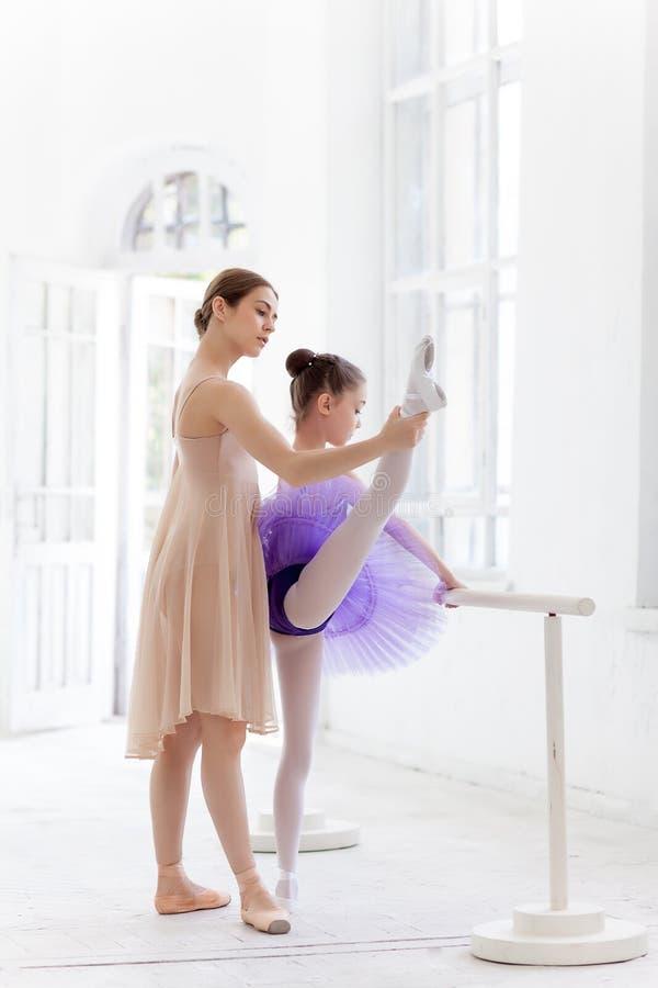 A bailarina pequena que levanta na barra do bailado com o professor pessoal no estúdio da dança imagem de stock