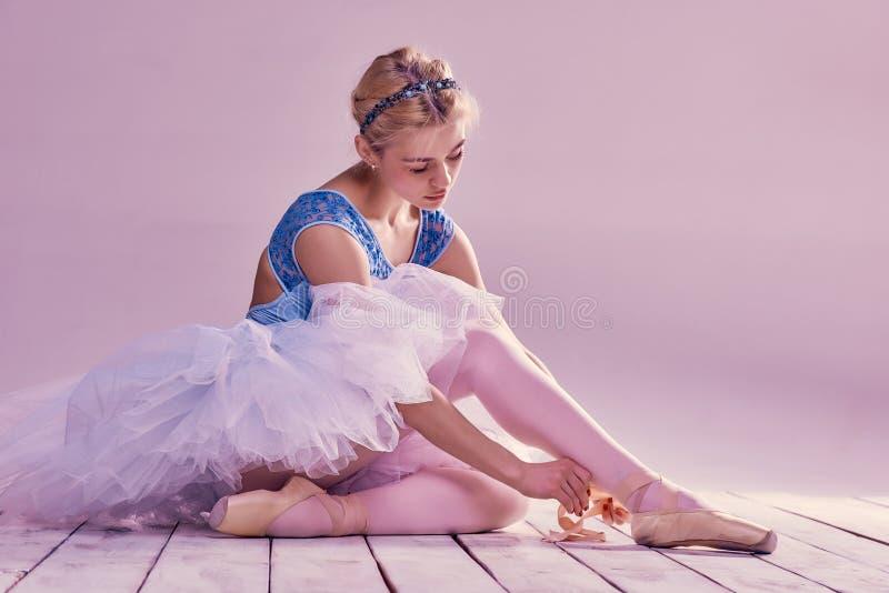 Bailarina profesional que pone en sus zapatos de ballet fotos de archivo libres de regalías
