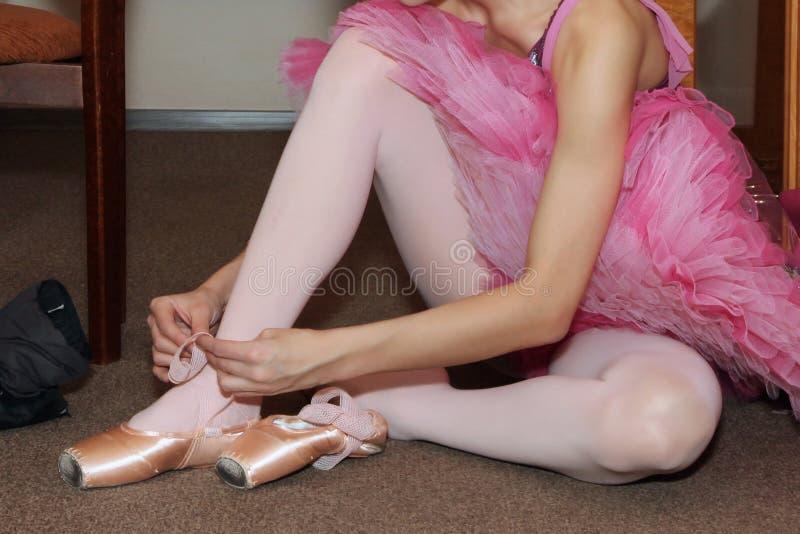 Bailarina que amarra sapatas de Pointe fotografia de stock