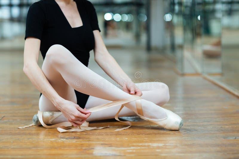 Bailarina que amarra sapatas do pointe na classe do bailado fotos de stock royalty free