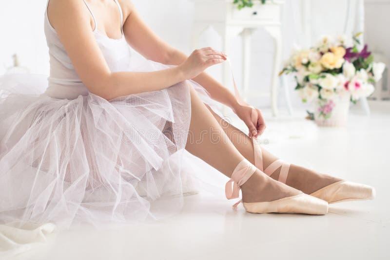 Bailarina que ata los zapatos de ballet del pointe Cierre para arriba foto de archivo