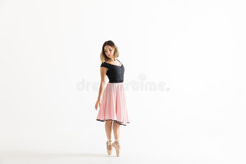 Bailarina que está na ponta do pé ao ensaiar sobre Backgr branco fotos de stock royalty free