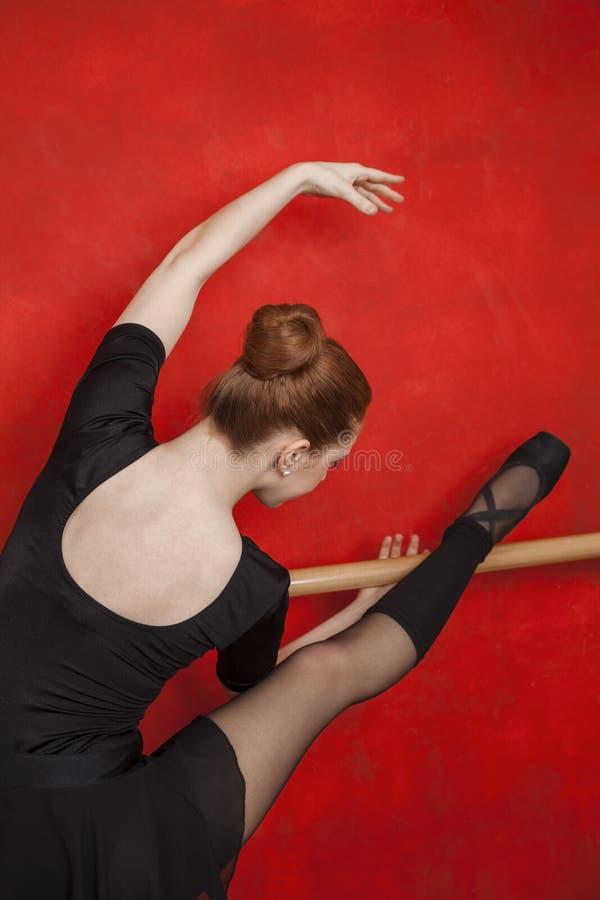 Bailarina que estica em Barre Against Red Wall fotografia de stock