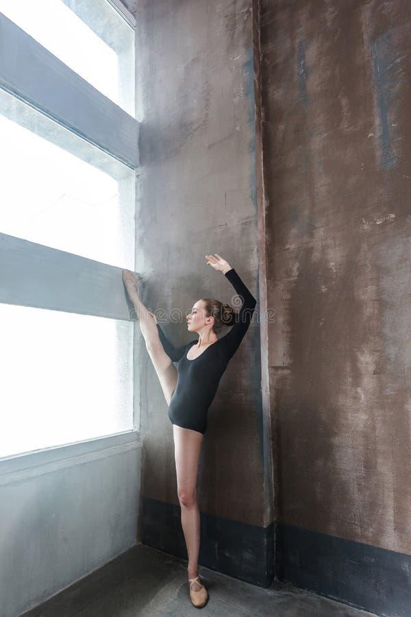 Bailarina que hace ejercicio aeróbico cerca de ventana de la luz del sol fotos de archivo