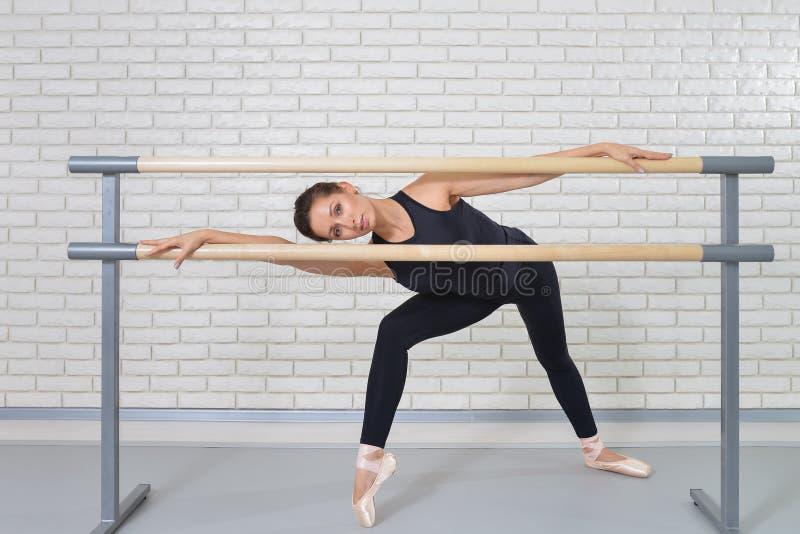 Bailarina que levanta perto da barra no estúdio do bailado, retrato completo do comprimento do dançarino bonito da mulher que olh fotografia de stock