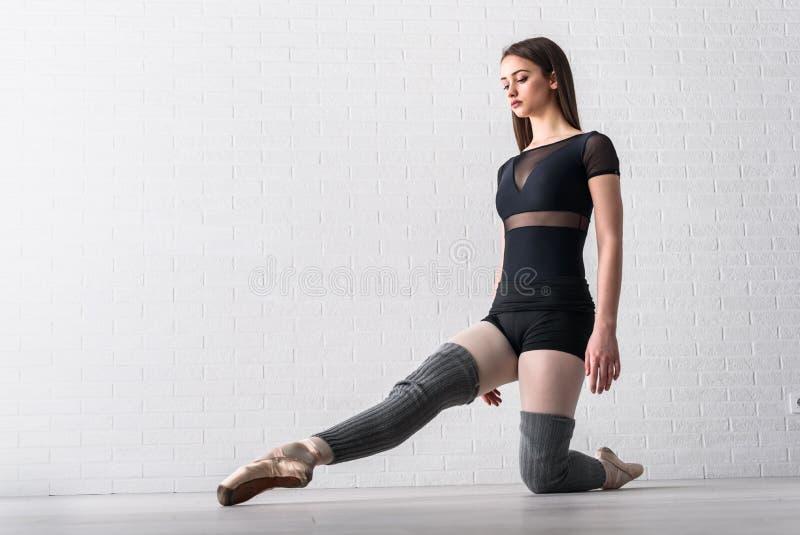 Bailarina que pratica no assoalho de seu estúdio da arte fotos de stock