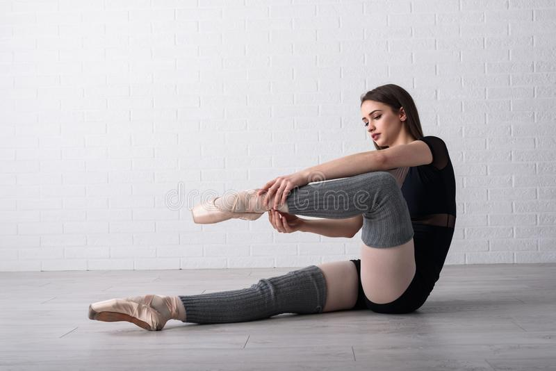 Bailarina que pratica no assoalho de seu estúdio da arte foto de stock