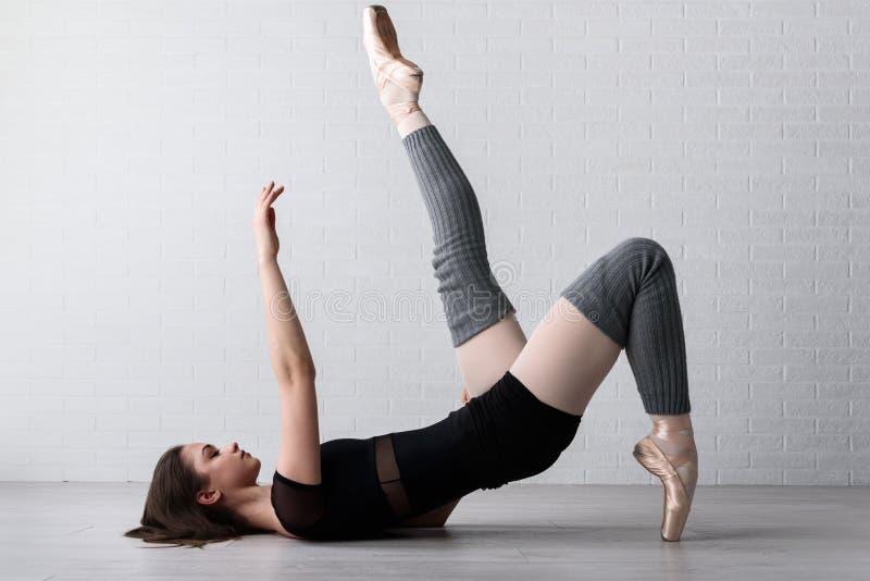 Bailarina que pratica no assoalho de seu estúdio da arte imagem de stock
