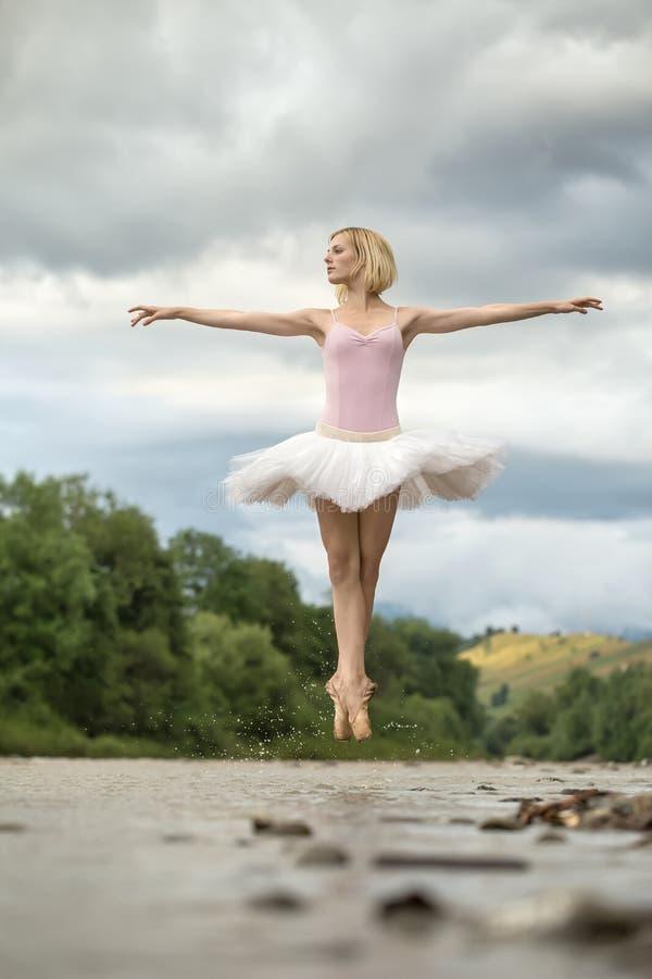A bailarina que salta acima do rio imagem de stock