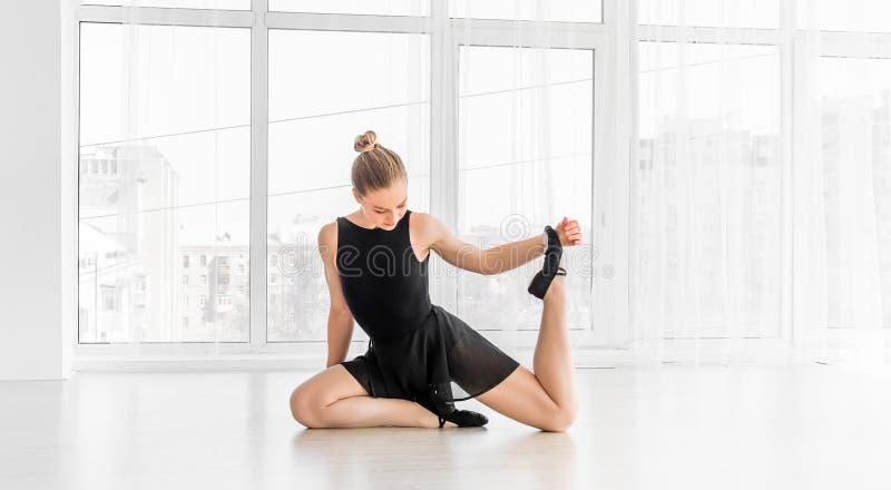 Bailarina que senta-se na ponta do pé no assoalho imagens de stock