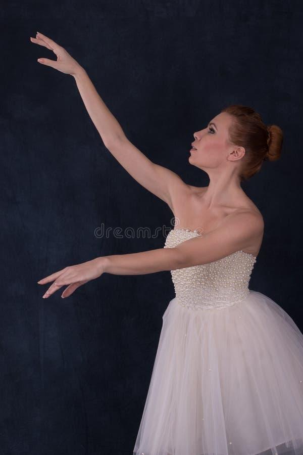 A bailarina que veste um vestido branco clássico dança em um b escuro fotos de stock royalty free