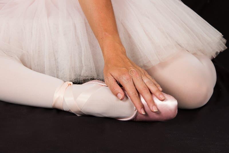 A bailarina senta-se para baixo no assoalho para pôr sobre deslizadores com mãos para o pe imagem de stock