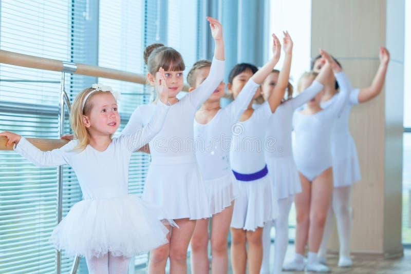 Bailarinas novas que ensaiam na classe do bailado Executam exercícios coreográficos diferentes Estão em diferente imagens de stock