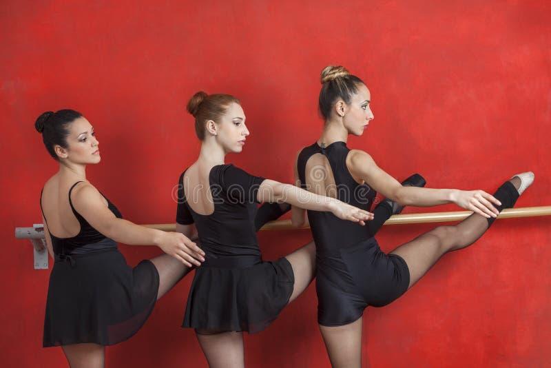 Bailarinas que executam em Barre Against Red Wall imagem de stock
