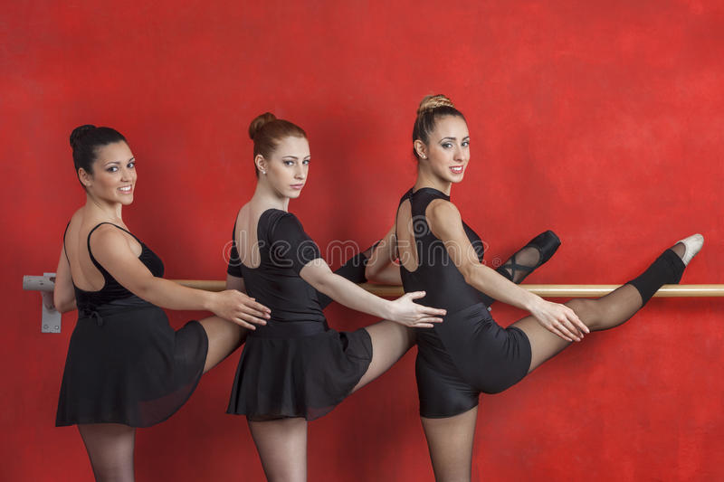 Bailarinas seguras que praticam em Barre Against Red Wall fotografia de stock royalty free
