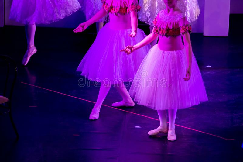 Bailarines de ballet bajo luz púrpura con los vestidos clásicos que realizan un ballet en fondo de la falta de definición fotos de archivo libres de regalías