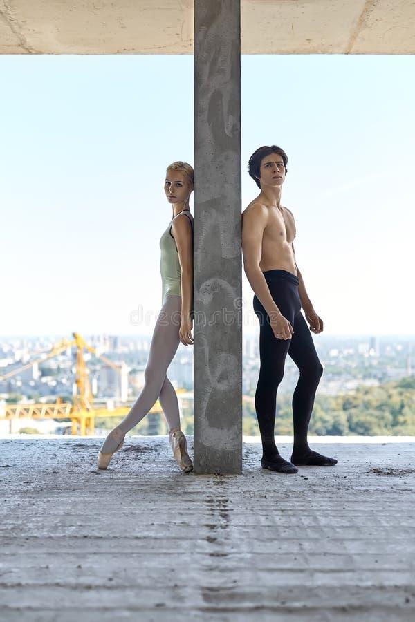Bailarines de ballet que presentan en el edificio inacabado foto de archivo