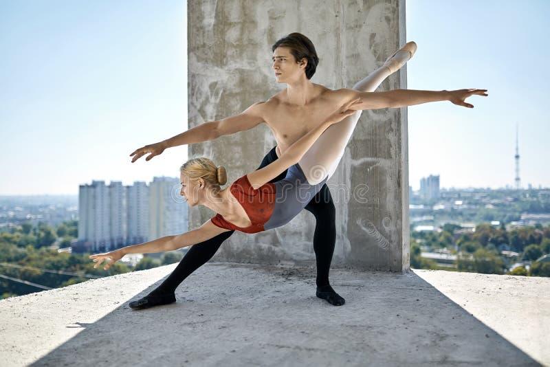 Bailarines de ballet que presentan en el edificio inacabado fotografía de archivo