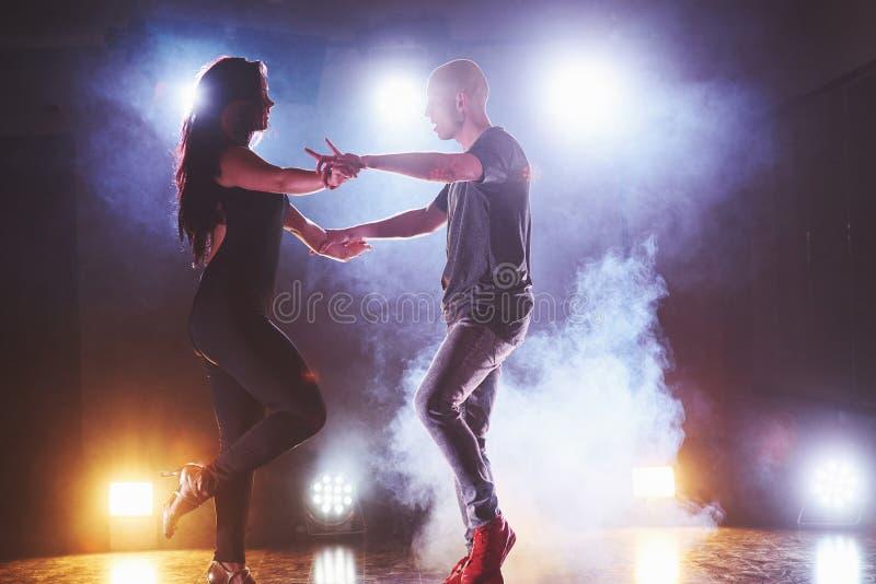 Bailarines expertos que se realizan en el cuarto oscuro debajo de la luz y del humo del concierto Pares sensuales que realizan un imagen de archivo