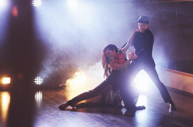 Bailarines expertos que se realizan en el cuarto oscuro debajo de la luz y del humo del concierto Pares sensuales que realizan un foto de archivo libre de regalías
