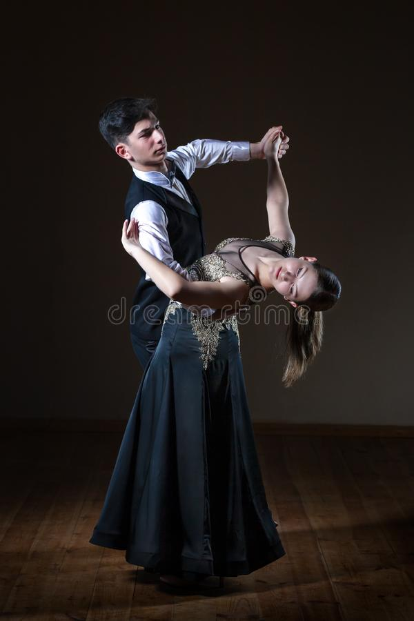 Bailarines jovenes hermosos en el sal?n de baile aislado en fondo negro fotografía de archivo