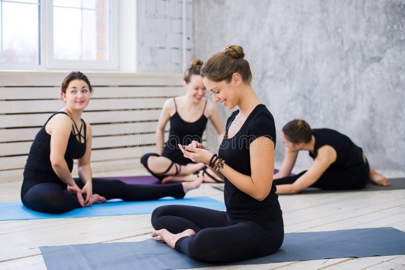 Bailarines o clase felices lindos de la yoga que toma una rotura de su entrenamiento y establecimiento de una red social con un t imágenes de archivo libres de regalías
