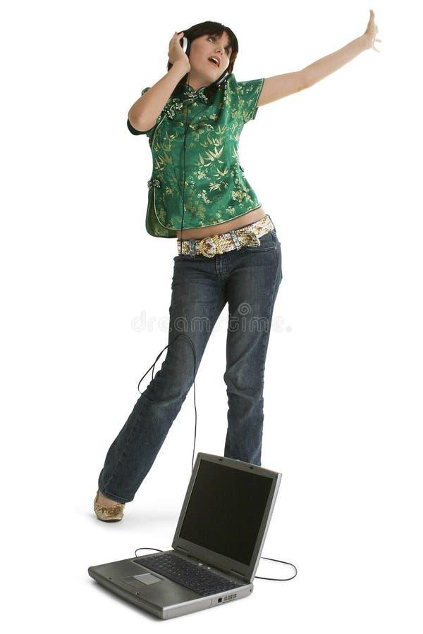 Baile adolescente de la muchacha con la computadora portátil y los auriculares fotografía de archivo libre de regalías