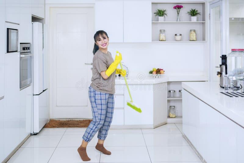 Baile bonito del ama de casa con una escoba en cocina fotografía de archivo libre de regalías