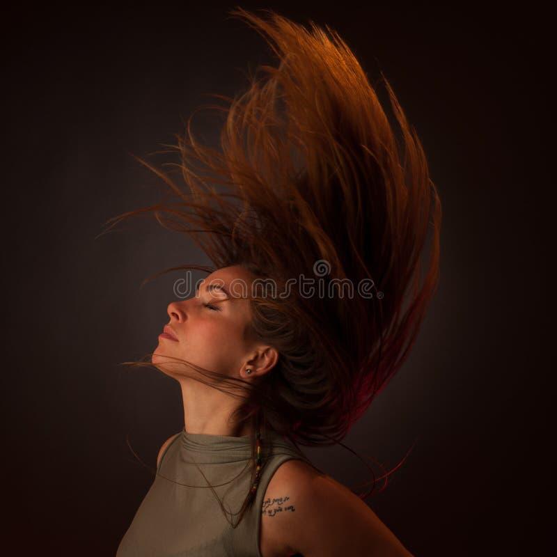Baile caucásico moreno joven de la mujer y su pelo que atraviesan el aire foto de archivo libre de regalías