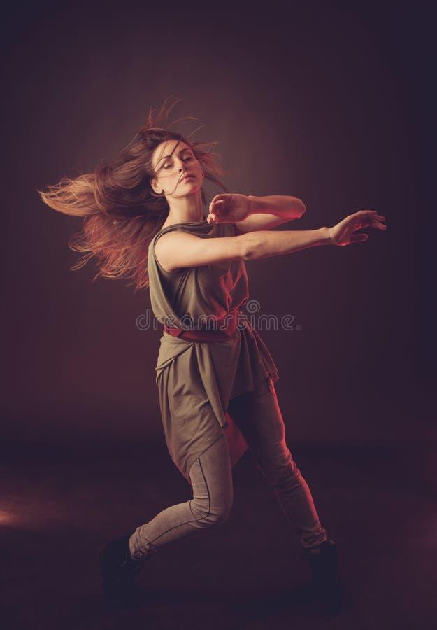 Baile caucásico moreno joven de la mujer y su pelo que atraviesan el aire fotografía de archivo libre de regalías