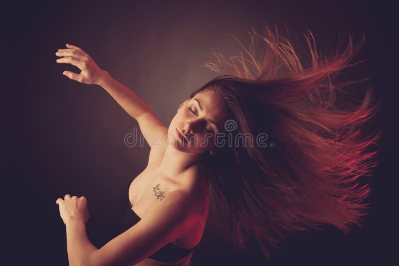 Baile caucásico moreno joven de la mujer y su pelo que atraviesan el aire imagenes de archivo
