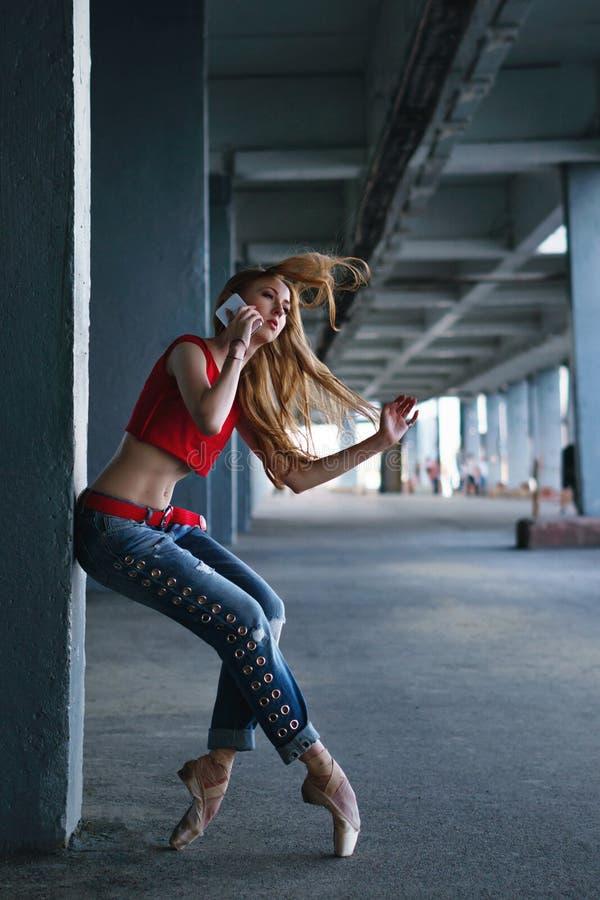 Baile de la bailarina con un teléfono celular Funcionamiento de la calle foto de archivo libre de regalías
