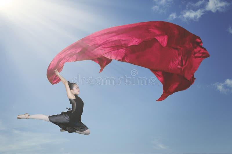 Baile de la bailarina con una tela roja en el cielo imagenes de archivo