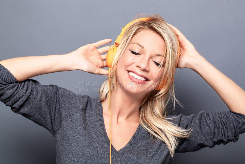 Baile de la muchacha en escuchar la música en los auriculares a relajarse fotos de archivo libres de regalías
