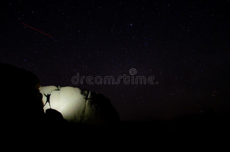 Baile de la muchacha en una roca en la noche foto de archivo