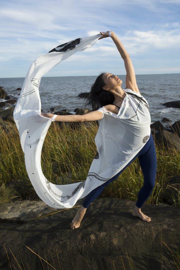Baile de la mujer con la tela blanca en la playa en Connecticut foto de archivo